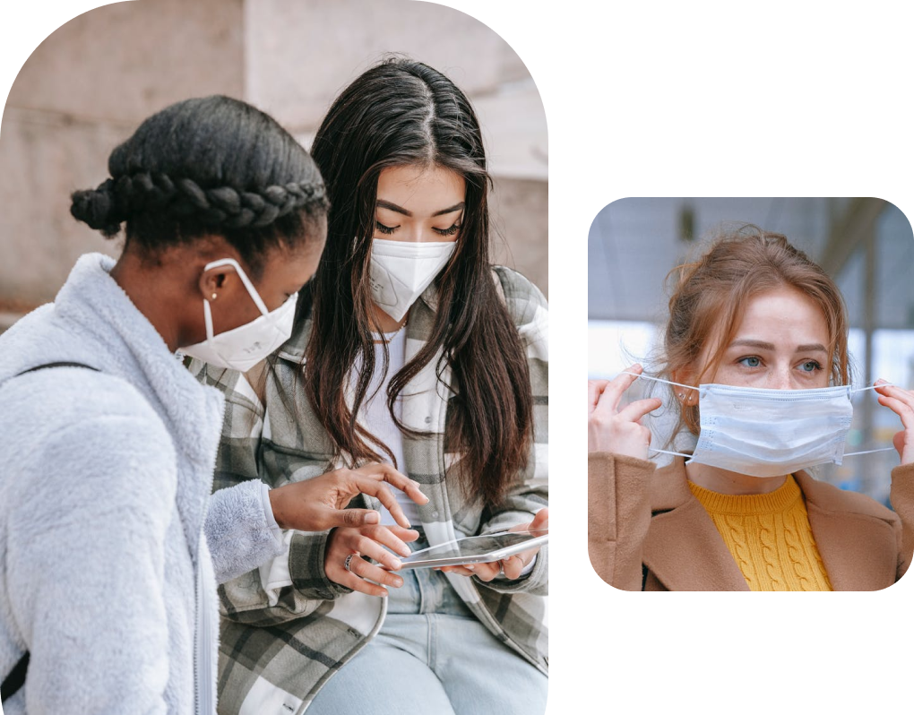 Two people wearing face masks looking at a phone and a person putting on a mask